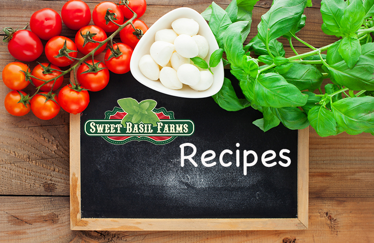 Italian food ingredients - tomatoes, basil, olives, olive oil, garlic, peppercorns and mozzarella on rustic wooden background, with chalkboard, top view